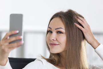 Close up of cheerful woman in office making selfie
