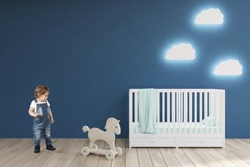 Boy in a baby's room, blue walls