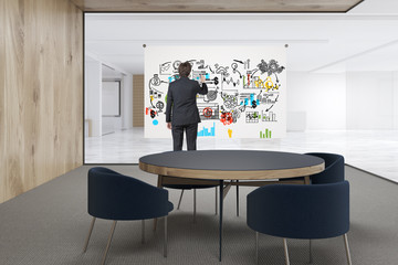 man drawing a poster in an office
