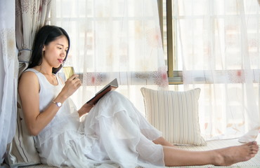 Girl reading a book by a bay window