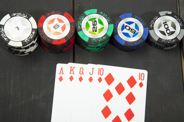 Combination of cards royal flush, poker game on black wooden table