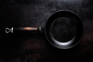 empty black cast iron pan on dark metal background may be used for menu or recipe or for culinary background