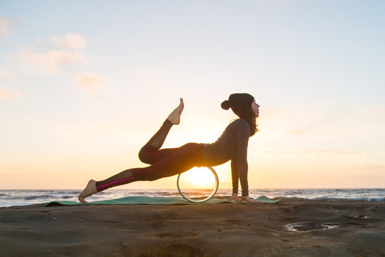 Girl in red bottoms, gray jacket and black hat doing yoga on a green yoga mat near the ocean at sunset with yoga wheel
