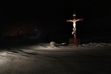 Krzyż z wizerunkiem Chrystusa na polach zimą.