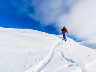 Mountaineer backcountry ski walking up along a snowy ridge with