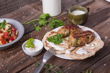 Kofta with flatbread on plate with salad