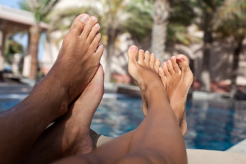 Closeup barefoot couple legs at the resort.