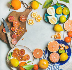 Natural fresh citrus fruits on wooden rustic board, colorful ceramic plates over grey marble table background, top view, copy space