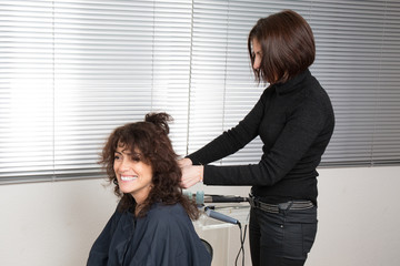 Professional hairdryer with electric hair curler by a hair dresser