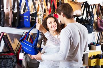 Couple choosing bags in shop