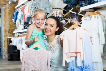 Woman with small child in kids apparel boutique