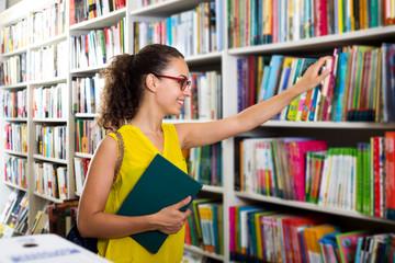 Woman taking literature books in store