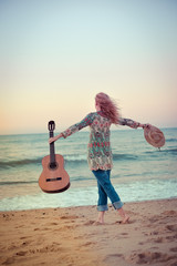 Back view of a beautiful blond female playing guitar on the beach, sunset sunny blue sky outdoors background