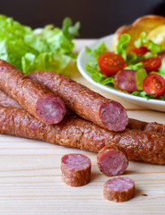 Smoked sausage with vegetables salad on a wooden board