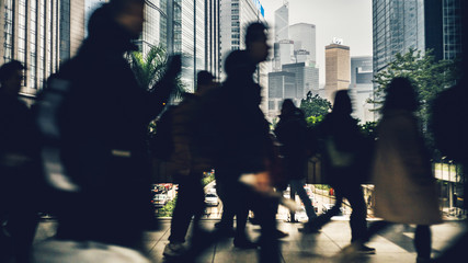 Commuters in Wan Chai using a Pedestrian crossing in the rush hour over Gloucester Rd, Hong Kong