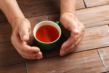 Hands of old senior with cup of tea on a wooden table