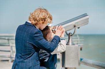 Two blonde hair brothers looks together in binoculars on the sea