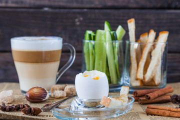 Soft Boiled egg with small spoon, coffee latte, sugar slices, cucumbers, bread for breakfast on old dark wooden table. Healthy food. Retro newspaper and cinnamon for decoration. Low key dark photo.