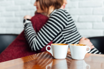 Two cups of coffee for two embracing women