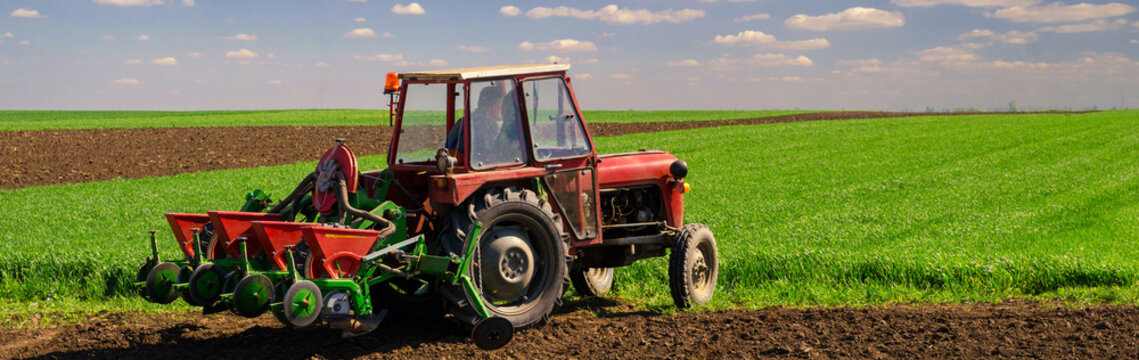 Farmer with tractor sowing on agricultural fields on sunny sprin