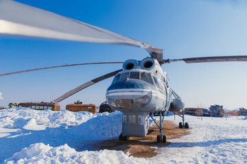 A large helicopter on the ground in winter