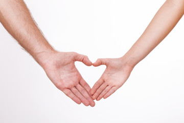 Young couple close to each other and smiling making heart shape made with their fingers isolated on white background.