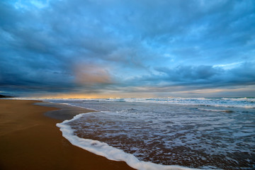 Seascape at sunset with waves on beach and heavy cloud cover.