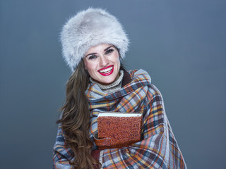 smiling modern woman in fur hat isolated on cold blue embracing