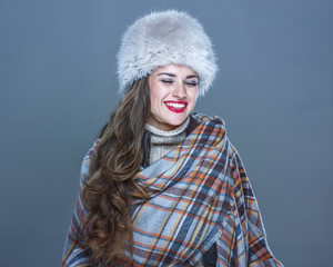 happy young woman in fur hat isolated on cold blue laughing