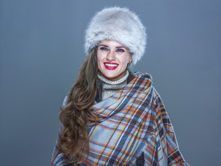 smiling trendy woman isolated on cold blue looking into distance