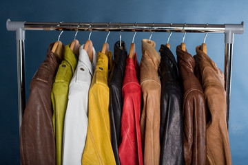 Different color leather jacket hanging on rack on blue background