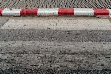 Concrete sidewalk with red and white