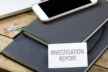 Card saying Investigation Report on note pad