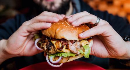 Fototapeta Young man eating a cheeseburger. obraz