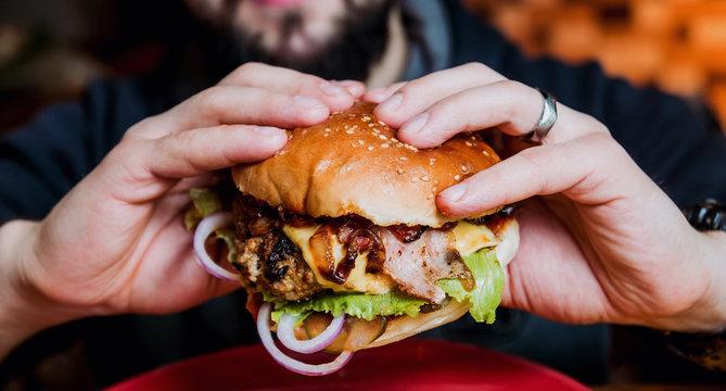 Young man eating a cheeseburger.