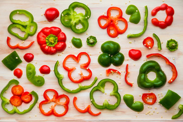 Food styling image design of red and green bell pepper slices on white wooden cutting board.