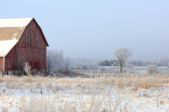 Rustic barn next to a field on a cold day.