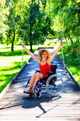 woman on a wheelchair rising her crutches