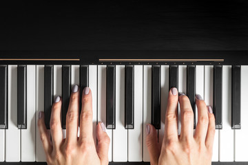 Closeup of hands playing piano. Music and hobby concept