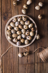 Quail eggs in a brown plate on a wooden table. Rustic Style. Eggs.  Easter photo concept. Copyspace