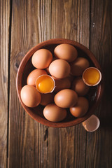 Brown eggs and broken eggs  in a brown ceramic bowl on  wooden table. Rustic Style. Eggs.  Easter photo concept. Copyspace
