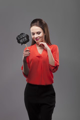 Pretty sexy fashion sensual brunette woman posing on gray background dressed in red shirt, holding paper party sticks. Love her