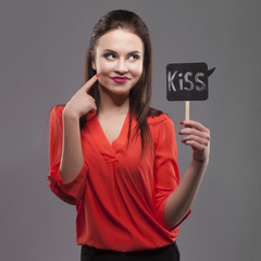 Pretty sexy fashion sensual brunette woman posing on gray background dressed in red shirt, holding paper party sticks. kiss