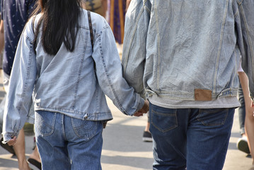 couple hold one's hand at plaza