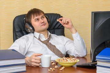 The man sits back in the office, eating popcorn and listening to music