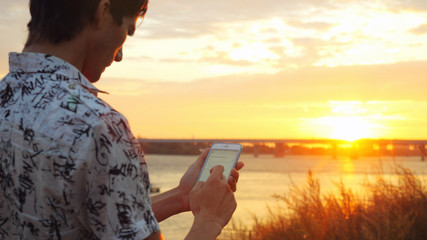 Young handsome man stands on the seashore at beautiful sunset using mobile phone on the bridge background