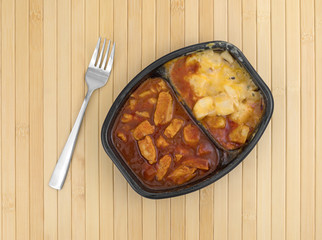 Microwaved TV dinner of chicken chunks in barbecue sauce plus potatoes atop a wood place mat with a fork to the side.