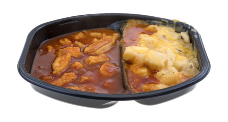 TV dinner of chicken chunks in barbecue sauce plus potatoes isolated on a white background.