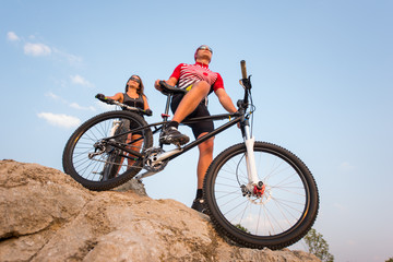 Bottom view of a mountain bike and the rider on it against the blue sky. Near is a girl with a bicycle and looks into the distance