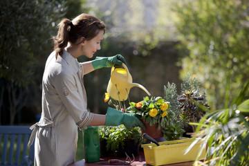 femme qui arrose des fleurs dans un jardin